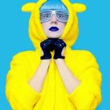 Muchacha loca del oso de peluche en una sudadera con capucha brillante en un fondo azul co Foto de archivo