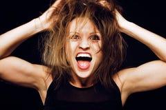 Muchacha loca tonta joven con el pelo ensuciado que hace caras estúpidas en el fondo negro, concepto de la gente de la forma de v Fotos de archivo