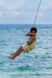 Muchacha local que balancea en un oscilación de la cuerda en el pueblo de Lavena en Taveuni Fotografía de archivo