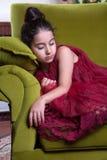 Muchacha lovlely de Oriente Medio linda con el vestido rojo oscuro y el pelo recogido que presentan y liying en interior verde de Foto de archivo