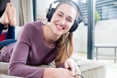 Muchacha magnífica alegre con los auriculares que se acuestan en sala de estar Imagenes de archivo