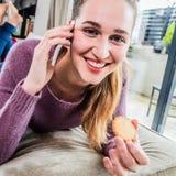 Muchacha magnífica alegre con una galleta que habla en su teléfono Foto de archivo libre de regalías