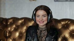 Muchacha magnífica con los auriculares estéreos que miran la cámara y la sonrisa almacen de video