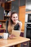 Muchacha magnífica feliz que se relaja en sostener una tableta en cocina Foto de archivo