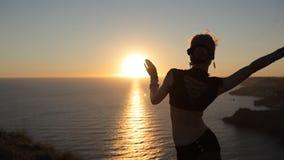 Muchacha magnífica que baila danza oriental en la puesta del sol almacen de video