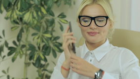Muchacha magnífica que habla en el teléfono móvil en oficina metrajes