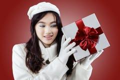 Muchacha magnífica que sostiene un regalo en fondo rojo Imagenes de archivo