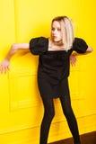 Muchacha magra que presenta en fondo amarillo Fotografía de archivo libre de regalías