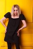 Muchacha magra que presenta en fondo amarillo Fotografía de archivo
