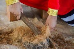 Muchacha maldiva que usa el cepillo para hacer el petróleo bruto para hacer cuerdas a mano imagen de archivo