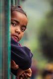 Muchacha malgache que mira de una ventana del tren Fotos de archivo