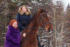 Muchacha, mamá y caballo del adolescente en un invierno Fotografía de archivo libre de regalías