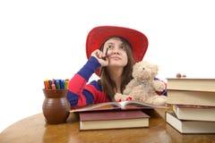 Muchacha meditativa joven con el sombrero rojo y su oso de peluche en la tabla Imagenes de archivo