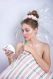 Muchacha-melcocha con una almohada y un despertador en su afra de las manos Foto de archivo