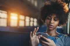 Muchacha mezclada linda en tren que charla vía smartphone Fotografía de archivo libre de regalías