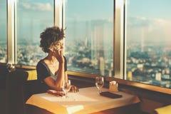 Muchacha mezclada que habla en el teléfono en restaurante Foto de archivo libre de regalías