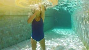 Muchacha milenaria del inconformista joven en flotador asperjado del buñuelo en la piscina, mirada sonriente en la cámara Mujer f almacen de metraje de vídeo