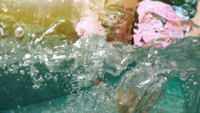 Muchacha milenaria del inconformista joven en flotador asperjado del buñuelo en la piscina, mirada sonriente en la cámara Mujer f almacen de video