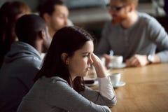 Muchacha milenaria trastornada frustrada que se sienta solamente en la tabla en café Imagen de archivo