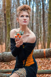 Muchacha misteriosa hermosa en un vestido en el bosque del otoño con los árboles de mandarina Imagenes de archivo