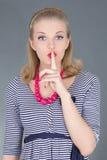 Muchacha modela atractiva en vestido rayado con el dedo en los labios Imagen de archivo libre de regalías