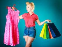 Muchacha modela con los panieres que compra el vestido de la ropa Foto de archivo