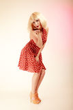 Muchacha modela en el vestido retro de la peluca rubia que sopla un beso Imagen de archivo libre de regalías
