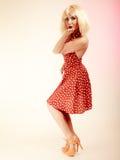 Muchacha modela en el vestido retro de la peluca rubia que sopla un beso Imagenes de archivo