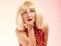 Muchacha modela en el vestido retro de la peluca rubia que sopla un beso Foto de archivo libre de regalías