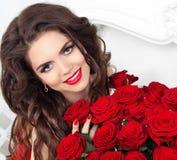 Muchacha modelo de la belleza con maquillaje, pelo largo y rosas rojas hermosas Imagenes de archivo