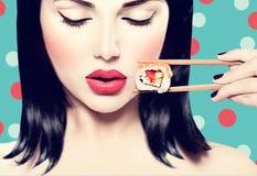 Muchacha modelo de la belleza que come el rollo de sushi Imagen de archivo