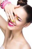 Muchacha modelo hermosa con maquillaje coloreado brillante y esmalte de uñas en la imagen del verano Cara de la belleza Clavos co foto de archivo
