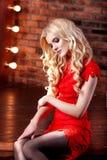 Muchacha modelo hermosa en un fondo rojo La belleza de una mujer Fotografía de archivo