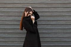 Muchacha modelo joven de moda en cubiertas negras de la capa imagenes de archivo
