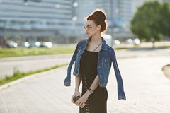 Muchacha modelo morena elegante y hermosa en una chaqueta de los vaqueros, en vestido negro de moda y en vidrios de moda, con imágenes de archivo libres de regalías