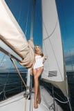 Muchacha modelo rubia zanquilarga atractiva y fasionable con el cuerpo perfecto en el bikini y la camiseta blanca que presentan c imagen de archivo