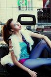 Muchacha moderna adolescente del modelo de manera que se sienta en estudio Imagenes de archivo