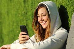 Muchacha moderna del adolescente que usa un teléfono elegante en un parque Fotografía de archivo libre de regalías