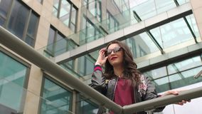Muchacha moderna en gafas de sol cerca de un vidrio de edificio almacen de video