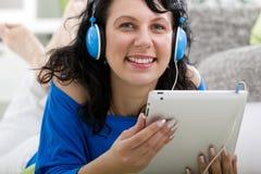 Muchacha moderna joven que pone en sofá con la tableta electrónica Imagenes de archivo