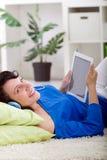 Muchacha moderna que pone en sofá con la tableta electrónica Foto de archivo libre de regalías