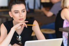 Muchacha moderna que sueña delante de su ordenador portátil Imagen de archivo libre de regalías