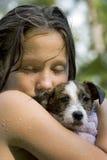 Muchacha mojada que abraza su perrito Fotos de archivo libres de regalías