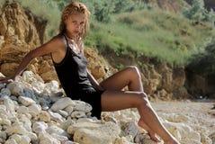 Muchacha mojada que se sienta en el Pebble Beach Fotos de archivo libres de regalías