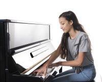 Muchacha morena adolescente y piano vertical negro en estudio Foto de archivo