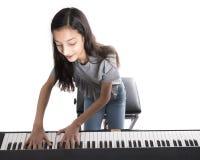 Muchacha morena adolescente y piano vertical negro en estudio Imagen de archivo libre de regalías