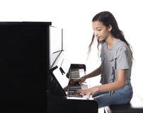 Muchacha morena adolescente y piano vertical negro en estudio Imagen de archivo