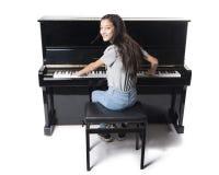 Muchacha morena adolescente y piano vertical negro en estudio Fotos de archivo libres de regalías