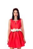 Muchacha morena adorable en rojo aislada en un fondo blanco Foto de archivo