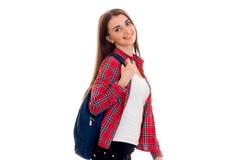 Muchacha morena alegre elegante del estudiante con la mochila azul que mira y que sonríe en la cámara aislada en el fondo blanco Fotos de archivo libres de regalías